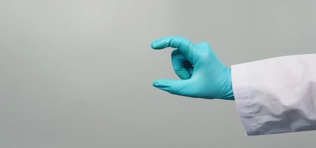Mão é segurar o gesto e usar vestido de médico e luva médica azul sobre fundo cinza.