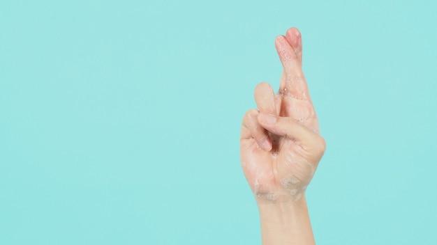 Mão é um sinal de boa sorte e tem bolhas de sabão em um fundo verde menta ou azul tiffany