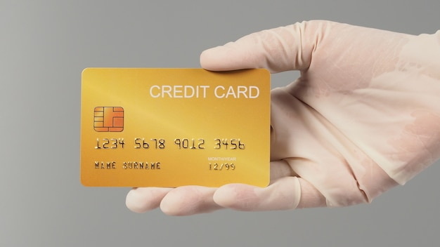 Mão é usar luva médica branca e segurando o cartão de crédito ouro isolado no fundo cinza.