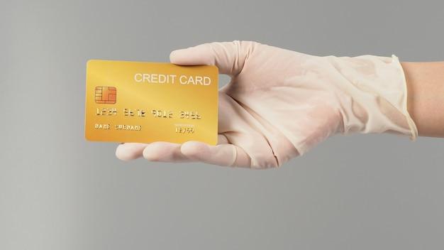 Mão é usar luva médica branca. segurando e mostre o cartão de crédito ouro isolado no fundo cinza.