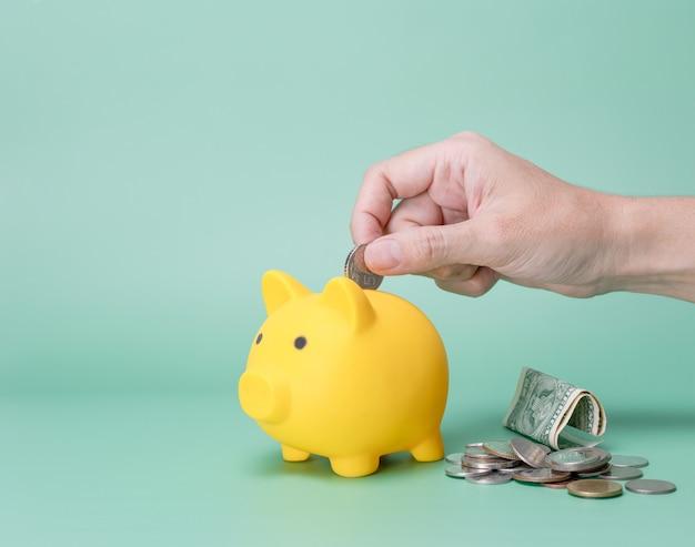 Mão economizando dinheiro no cofrinho