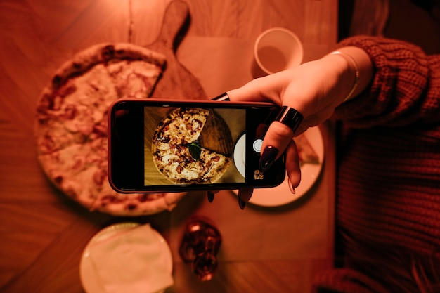 Mão em close tirando foto de pizza