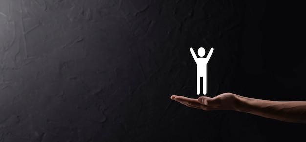 Mão em fundo escuro com ícone humano