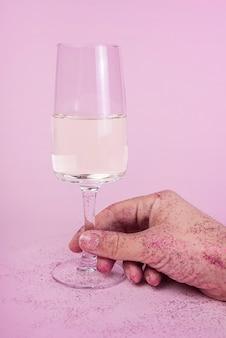 Mão em lantejoulas segurando a taça de champanhe na mesa