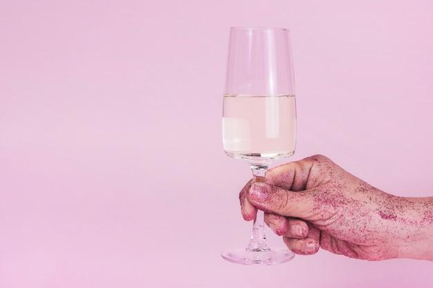 Mão em lantejoulas segurando a taça de champanhe