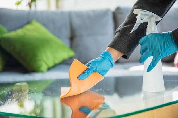 Mão em luvas de desinfecção de superfícies com desinfetante em casa. limpeza contra o vírus da pneumonia.