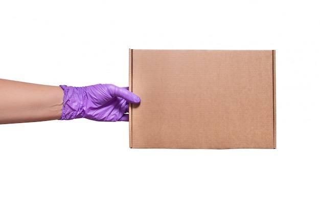 Mão em luvas de látex, segurando a caixa de papelão