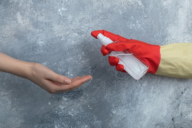 Mão em luvas de proteção borrifando etanol para mulher.