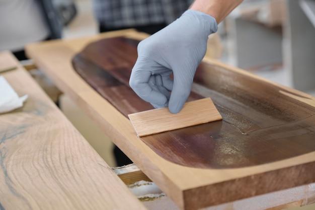 Mão em luvas de proteção com acabamento de capa protetora para madeira