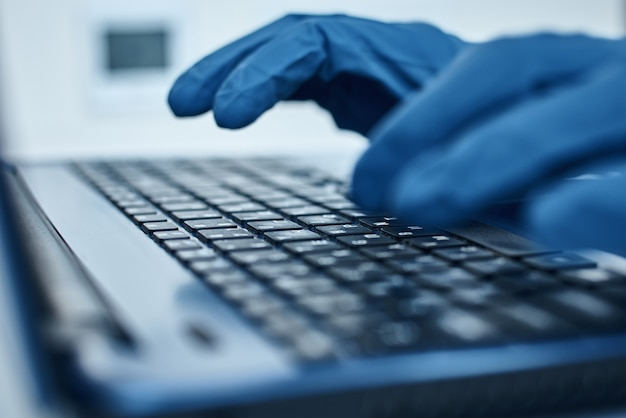 Mão em luvas de proteção digitando no teclado do laptop. proteção contra o conceito de coronavírus covid-19