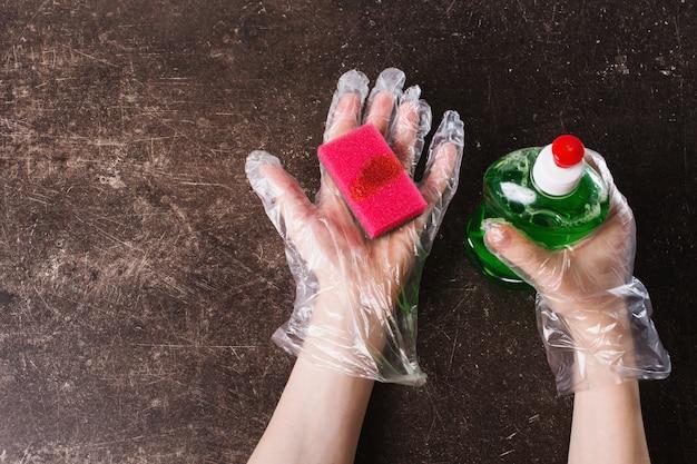 Mão em luvas higiênicas plásticas com uma esponja em um fundo de mármore escuro. arrumar a casa. lave a louça com detergente