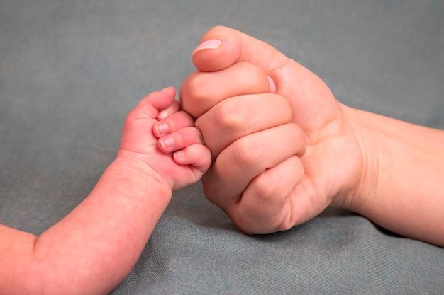 Mão em punho do bebê recém-nascido e punho dos pais juntos