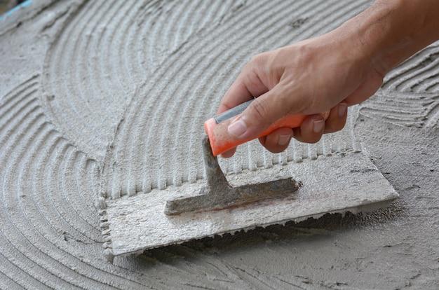 Mão em ser preso com cimento, faça trabalho de cimento, aplique cimento (em cima de uma superfície)