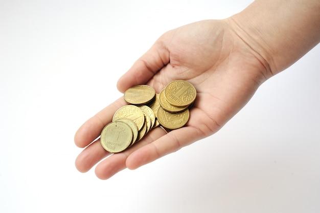 Mão em um fundo branco, segurando um punhado de moedas um hryvni