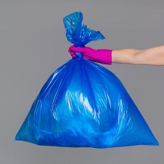 Mão em uma luva de borracha mantém um saco de plástico azul cheio de lixo.