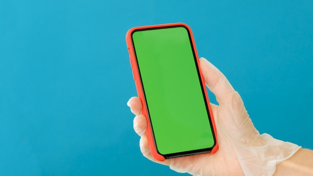Mão em uma luva de borracha segura um smartphone com uma tela verde