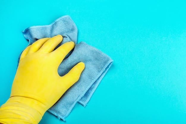 Mão em uma luva de borracha, segurando um pano e toalhetes em uma mesa azul