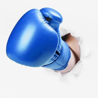 Mão em uma luva de boxe azul atravessou a parede de papel