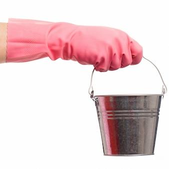 Mão em uma luva rosa segurando balde de prata