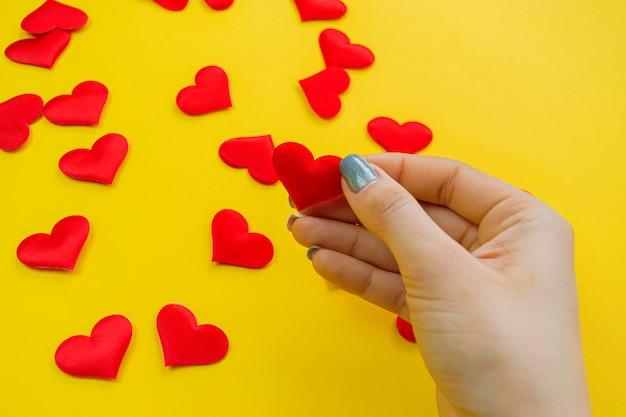 Mão em uma superfície amarela com corações