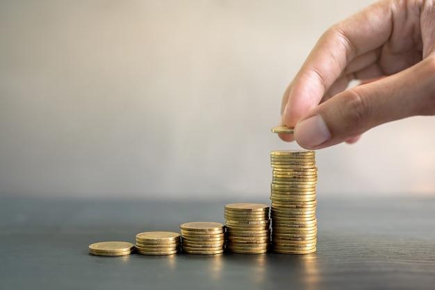 Mão empilhando moedas de ouro na mesa de madeira preta. negócios, finanças, marketing, conceito e design de comércio eletrônico