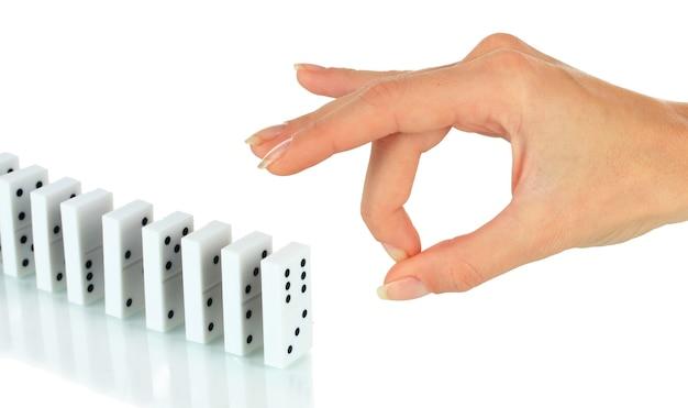 Mão empurrando dominó isolado no branco