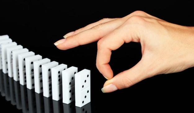 Mão empurrando dominó isolado no preto
