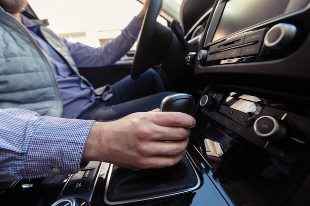 Mão empurrando o botão de energia para ligar o sistema de som do carro