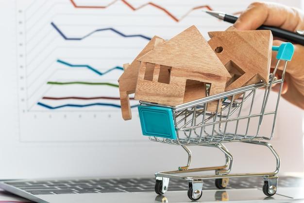 Mão empurre a casa de madeira para a frente no carrinho no computador portátil com documentos de gráfico de relatório para hipoteca de investimento imobiliário financeiro em compras online ou crédito de parcelamentos mensais de habitação de pagamento.