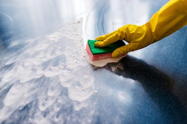 Mão enluvada limpa espuma e sujeira com um pano. limpeza.