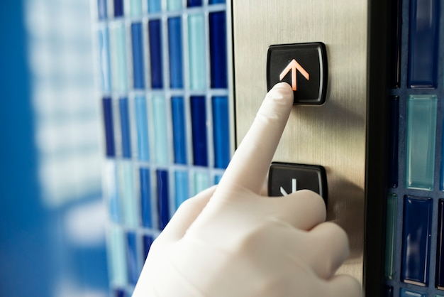 Mão enluvada pressionando um botão de elevador para evitar a contaminação por coronavírus