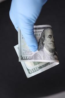 Mão enluvada segura conceito de doenças transmitidas por dinheiro de notas de cem dólares