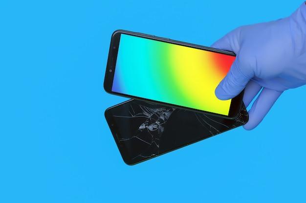 Mão enluvada segura novo smartphone substituindo um smartphone velho quebrado por uma tela rachada em um fundo azul