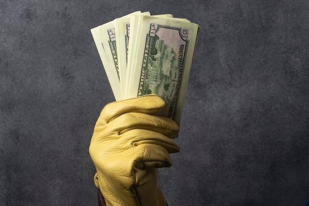 Mão enluvada segurando um maço de dólares