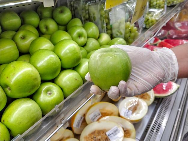 Mão enluvada segurando uma maçã verde, proteção contra coronavírus.