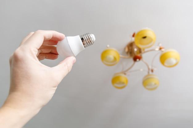 Mão enroscando nova lâmpada na lâmpada do teto