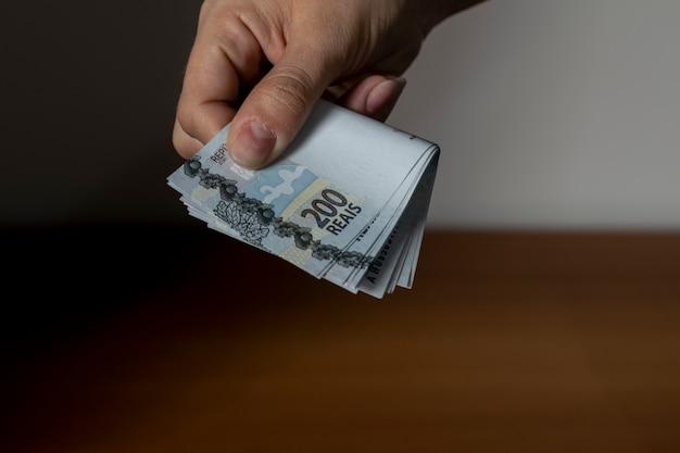 Mão entregando novas notas de dinheiro brasileiras
