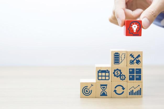 Mão escolha a cabeça do ícone do empresário no bloco de madeira.