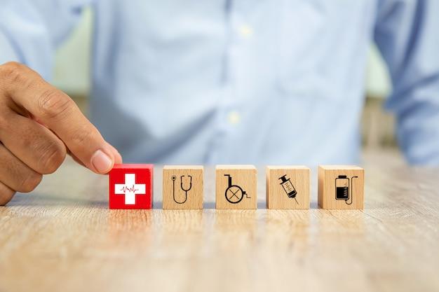 Mão escolha ícones de medicina e saúde no bloco de madeira.