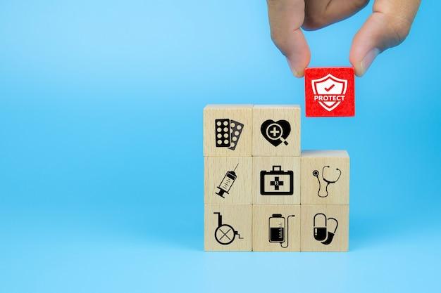 Mão escolhe ícone médico no cubo de blocos de brinquedo de madeira empilhados com outros símbolos médicos