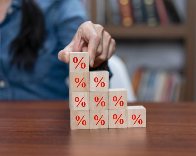 Mão escolhe o bloco de cubos de madeira com o símbolo de porcentagem do ícone