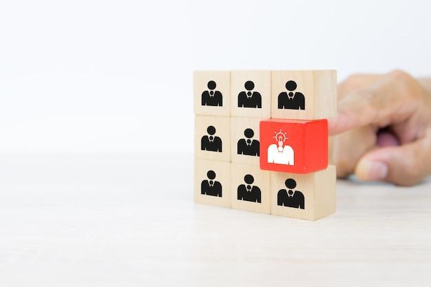 Mão escolhendo a cabeça de ícones de pessoas com uma lâmpada em blocos de brinquedo de madeira do cubo empilhados.