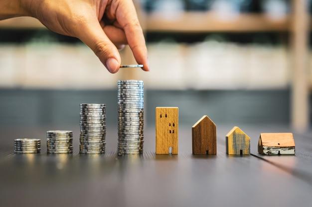 Mão, escolhendo a linha de dinheiro moeda na mesa de madeira e mini casa de madeira,