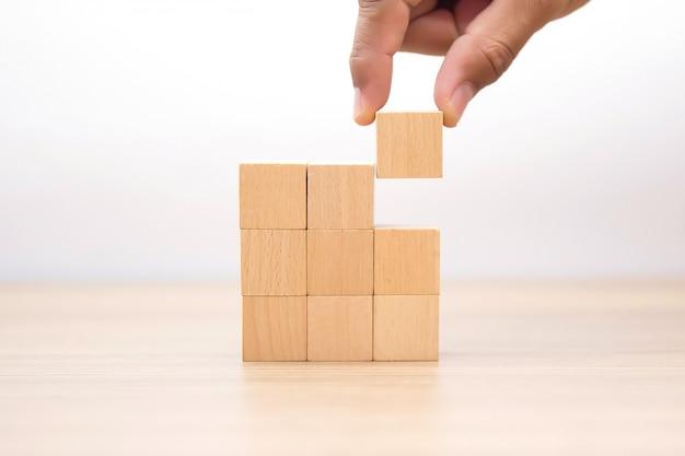 Mão escolhendo bloco de madeira com gráfico fora.