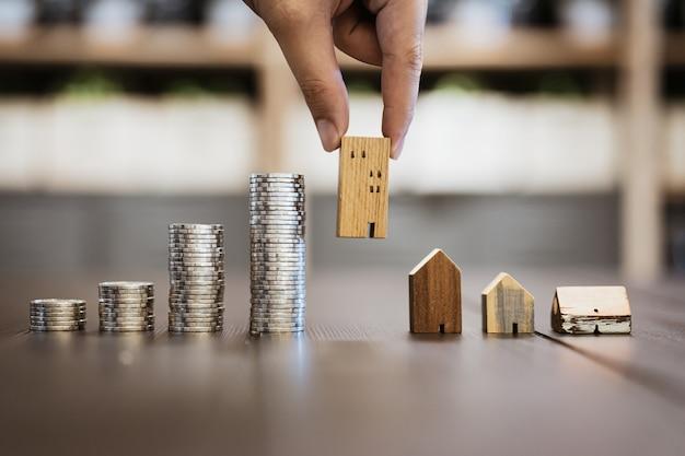 Mão escolhendo mini casa de madeira e linha de moedas na mesa de madeira