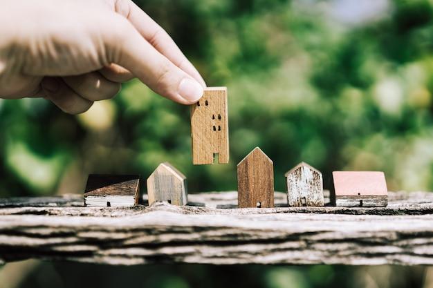 Mão escolhendo mini modelo de casa de madeira do modelo na mesa de madeira,