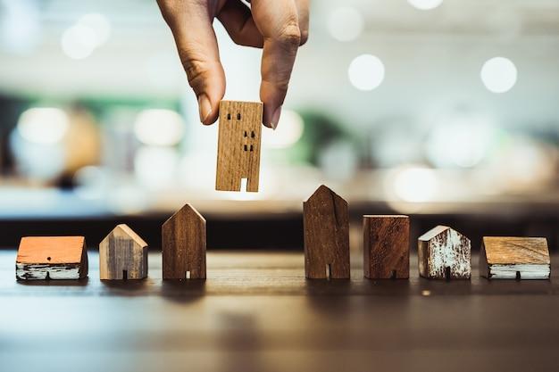 Mão escolhendo mini modelo de casa de madeira do modo na mesa de madeira