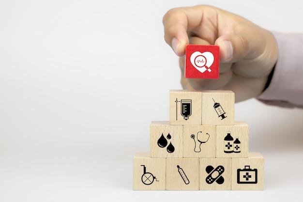 Mão, escolhendo o ícone de saúde na pilha de blocos de brinquedo de madeira do cubo na pirâmide com outros ícones médicos.