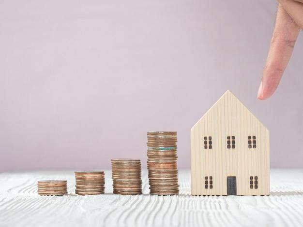 Mão escolhendo o modelo da casa de madeira e pilha de moedas na mesa de madeira branca, foco seletivo. planejando comprar um imóvel. escolha o que é melhor