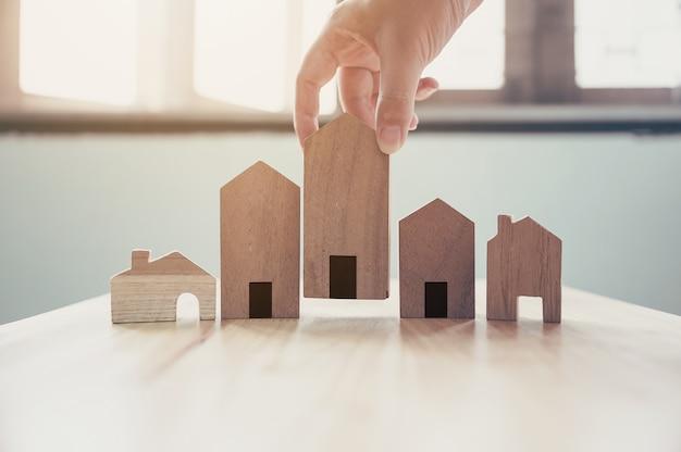 Mão, escolhendo o modelo de casa de madeira. hipoteca e investimento em imóveis